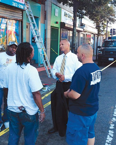 John Barros talking with workers on Dorchester Ave. Barros has been traveling to T stops, barbershops, grocery stores and basketball tournaments asking residents to engage in Stand Up Now, his campaign for better schools, safer communities and a cleaner environment.