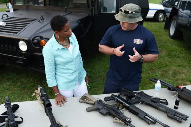 Rep. Donna Edwards (D-Md.) receives SWAT instructions from Laurel, Md., Police MPO Jeff Van Cleave during the town's annual National Night Out in Granville Gude Park on Tuesday, Aug. 6. The yearly event gives Laurel's law enforcement and rescue personnel an opportunity to meet with the community.