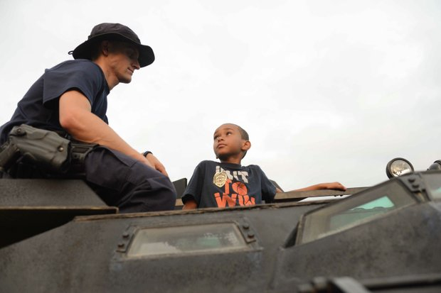 Joshua Jamieson, 8, talks with Officer Matt Jordan, a member of the Laurel, Md., Police Department SWAT team, atop an armored vehicle at the town's annual National Night Out in Granville Gude Park on Tuesday, Aug. 6. The yearly event gives Laurel's law enforcement and rescue personnel an opportunity to meet with the community.