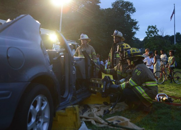 Members of the Laurel, Md., volunteer fire department dismantle a vehicle during a demonstration at the town's annual National Night Out in Granville Gude Park on Tuesday, Aug. 6. The yearly event gives Laurel's law enforcement and rescue personnel an opportunity to meet with the community.