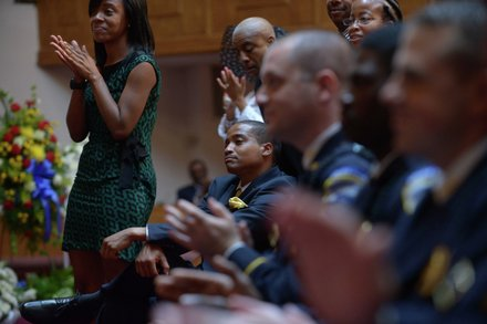 Family and friends stand and applaud after an emotional tribute offered by the grandchildren of the late James Bunn during his funeral service at Matthews Memorial Church in Southeast on Friday, Aug. 9. Bunn, chairman of the Congress Heights Main Streets Organization and the Ward 8 Business Council, died Aug. 1.