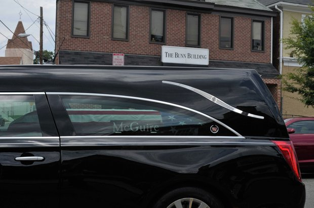 The hearse carrying the coffin of the late James Bunn rides past the Bunn Building en route to its final resting place at National Harmony Memorial Park in Largo, Md., on Friday, Aug. 9. Bunn, chairman of the Congress Heights Main Streets Organization and the Ward 8 Business Council, died Aug. 1.