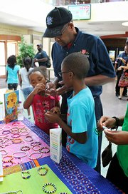 Kroc Center summer camp students sell products they made to a Salvation Army employee at the Dorchester center last week.