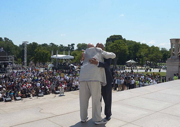 Radio personality Tom Joyner (left), hugs Rep. John Lewis (D-GA), on the steps of the Lincoln Memorial at the March on Washington 50th Anniversary on Sat., August 24.