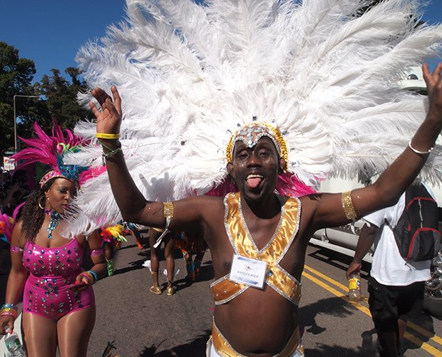 Boston Socaholics band leader Derric Sealy gets into the spirit of Carnival, leading his dancers in the parade to Franklin Park.
