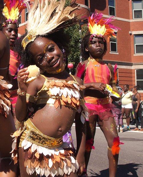 "Five-year-old Kalaiya Marshall Akhia (front) dances with Boston Socaholics. The Socaholics' 2013 theme was ""Sweet Escape."""