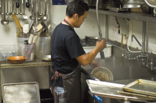 Young man washing dishes at a restaurant.