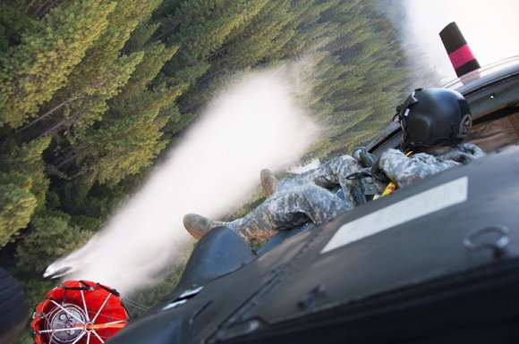 Soldiers battle wildfires at Yosemite National Park, California. Army Sgt. Chris Boni releases water from over head dousing the Rim fire below near Yosemite National Park, California, August 22, 2013.