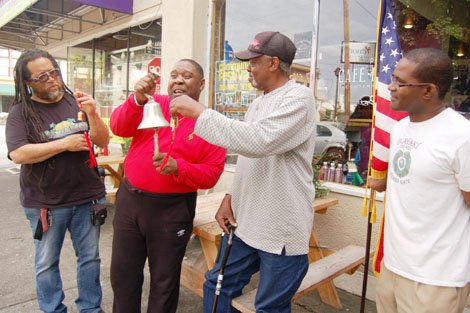 "Pastor E.D. Mondainé (second from left) joins a patron outside his soul food eatery ""Po' Shines"" in north Portland to symbolically ring the bells of freedom on the 50th anniversary of Martin Luther King's infamous ""I Have A Dream"" speech."