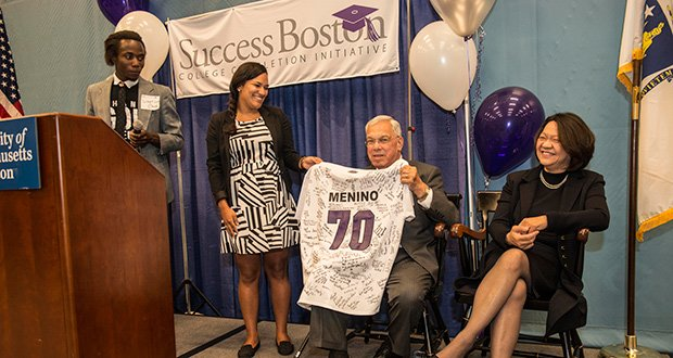 Boston Mayor Thomas M. Menino accepts a jersey signed by dozens of Boston Public Schools graduates now enrolled in college at the annual Success Boston kickoff at UMass Boston's Clark Athletic Center. The number 70 signifies Mayor Menino's goal of 70 percent college-completion among BPS students. (L-R) Tucker Gaye of Dorchester, a second-year student at UMass Boston; Annabel Cordero of Mission Hill, a senior at Emmanuel College; Boston Mayor Thomas M. Menino; and Dr. Pam Eddinger, new president of Success Boston partner Bunker Hill Community College. (Photo courtesy of the Boston Mayor's Office)