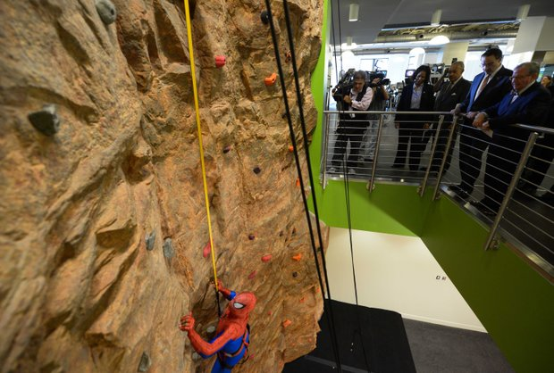 A man dressed as Spider-Man climbs the rock wall at the newly refurbished Anthony Bowen YMCA in Northwest D.C. after a ribbon-cutting ceremony on Monday, Sept. 9.
