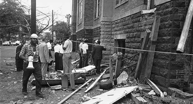 A civil defense worker and firemen walk through debris from an expolsion that struck the 16th street Baptist Church, killing and injuring several people, in Birmingham, Ala., on Sept. 15, 1963. The open doorway at right is where at least four persons are believed to have died.