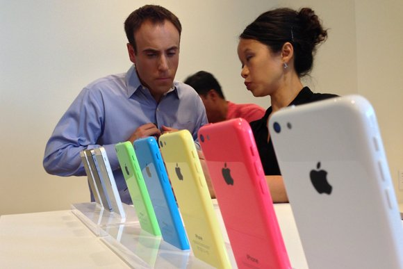An Apple employee demonstrates the newest iPhone offerings from Apple, Inc. following the tech giant's event in Cupertino, Tuesday, September 10th, 2013. Apple unveiled the iPhone 5S and iPhone 5C.