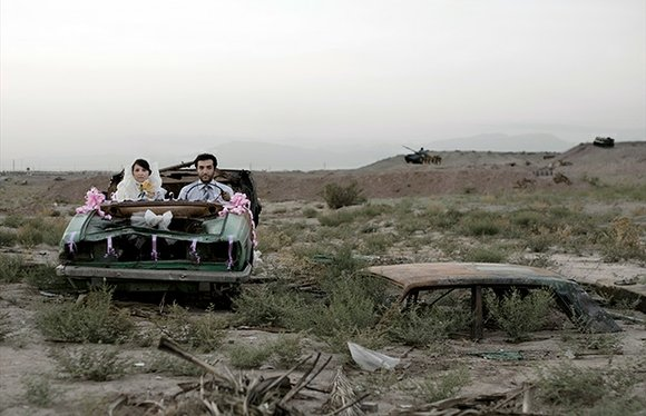 Young newlyweds gaze at the viewer from their beribboned wreck of a car, which stands alone in a battlefield. Iranian ...