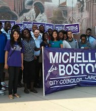 Standing above the first two letters of her name on the campaign banner, At-Large City Council candidate Michelle Wu joins supporters in Dudley Square.