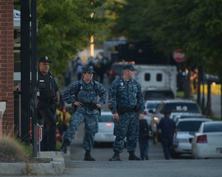 Military and federal police stand guard at the M Street entrance of the Washington Navy Yard on Monday, Sept. 16, after a gunman went on a rampage and killed 12 people.