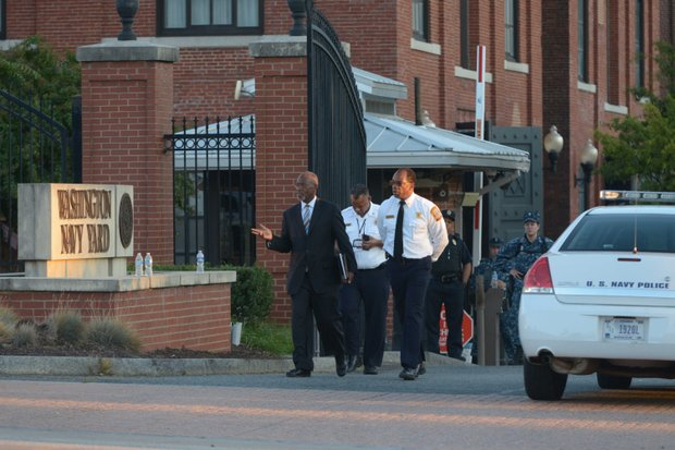D.C. Deputy Mayor Paul Quander and Fire Chief Kenneth Ellerbe leave the Washington Navy Yard on Monday, Sept. 16, after a shooting rampage at the Navy Yard left 13 people dead, including the suspected gunman.