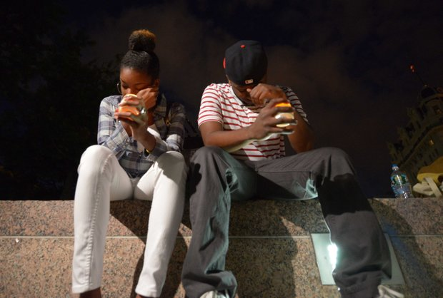 Jibir Johnson (right), 24 of Lanham, Md., and Brittnay Carter, 24 of Lanham, listen to speakers during a candlelight vigil at Freedom Plaza in Northwest on Monday, Sept. 16, to honor the victims of the Washington Navy Yard shooting.