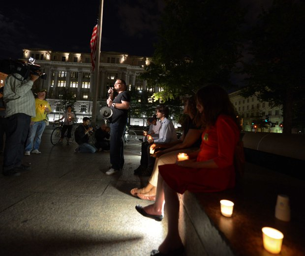 Eddie Weingart, 34, center, speaks to a small crowd gathered for a candle light vigil honoring the lives and shooting victims of the Navy Yard shooting  at Freedom Plaza in Northwest on  Monday, September 16.