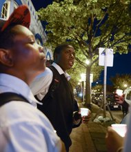 Dwayne Brooks (center), 15, a student at the Richard Wright Public Charter School for Journalism and Media Arts in D.C., stands in silence during a candlelight vigil for the victims of the Washington Navy Yard shooting at 8th and M streets in Southeast on Tuesday, Sept. 17.
