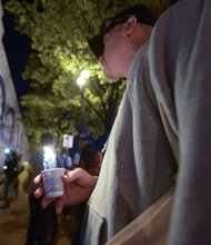 A man holds a candle during a vigil for the victims of the Washington Navy Yard shooting at 8th and M streets in Southeast on Tuesday, Sept. 17.
