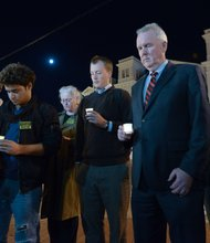 D.C. Council member Tommy Wells (center), Ward 6 Democrat, asks for a moment of silence during a candlelight vigil for the victims of the Washington Navy Yard shooting at 8th and M streets in Southeast on Tuesday, Sept. 17.