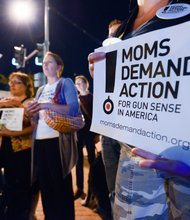 Gun-control advocates hold signs at a candlelight vigil for the victims of the Washington Navy Yard shooting at 8th and M streets in Southeast on Tuesday, Sept. 17.