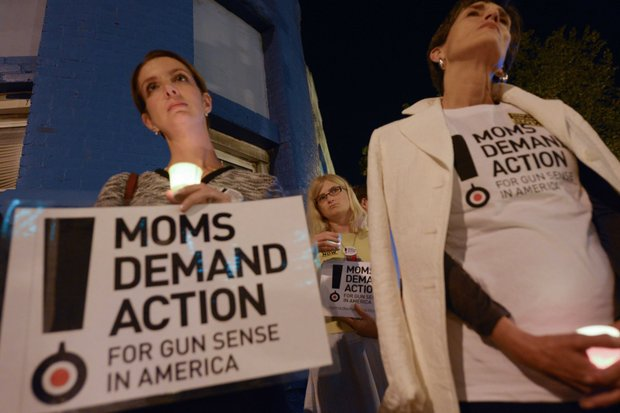 Shannon Watts (left), founder of Moms Demand Action, and Grace Terpstra stand in silence during a candlelight vigil for the victims of the Washington Navy Yard shooting at 8th and M streets in Southeast on Tuesday, Sept. 17.