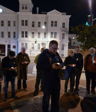 A small group stands in silence during a candlelight vigil for the victims of the Washington Navy Yard shooting at 8th and M streets in Southeast on Tuesday, Sept. 17.