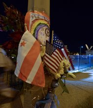 A man walks past a makeshift memorial at a lamppost on M Street in Southeast honoring the Washington Navy Yard victims on Tuesday, Sept. 17.