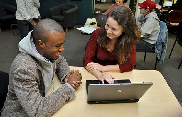 (L-R) Student Shatwuan Lewis works with Mallory Bram, one of the Bottom Line mentors helping students with college applications.