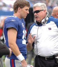 Eli Manning and offense coordinator Kevin McBride in a sideline meeting during their one-sided loss in Denver