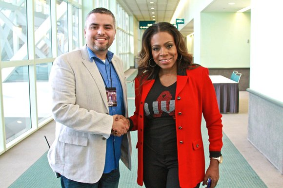 Celebrity host Sheryl Lee Ralph who is joined by West Coast Expo's Jose Torres, shows off one of the diva T-shirts she designed and sells to raise money to fight HIV/AIDS.