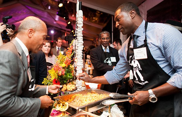 "Former New England Patriots player Eric Alexander serves food from Darryl's Corner Bar and Kitchen to Gov. Deval Patrick at the 16th ""Men of Boston Cook for Women's Health"" at the Codman Square Health Center on Sept. 26."
