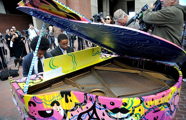 Two Boston Arts Academy students play a duet on the piano installed on City Hall Plaza.