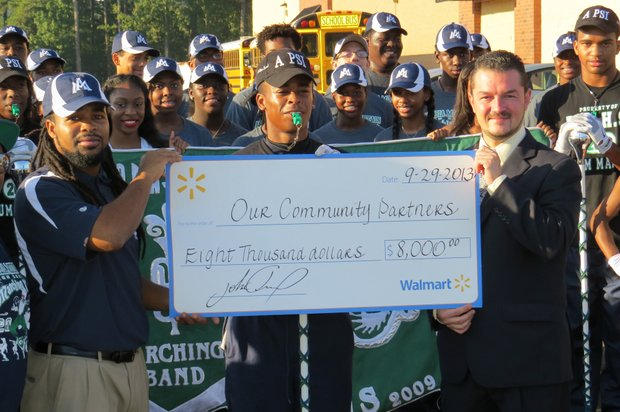 """Emanuel Johnson, Arabia Mountain High School Marching Rams """"Funk Machine"""" Band director, helps Stonecrest Walmart store manager John Moreno hold a big check board showing the $8,000 donated to 12 community partners in honor of the new store's grand opening. Arabia Mountain High received a $500 donation."""