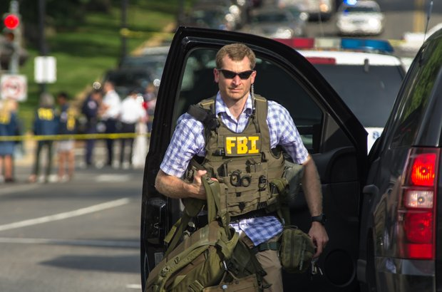 An FBI agent helps secure the scene Thursday afternoon after a woman was shot to death following a high-speed chase on Capitol Hill. The White House and U.S. Capitol were temporarily shut down during the incident.