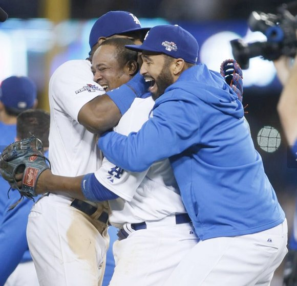 Los Angeles Dodgers Juan Uribe, center, and Matt Kemp, right, celebrate their 4-3 victory over the Atlanta Braves Tuesday night at Dodger Stadium to win their National League Division Series.