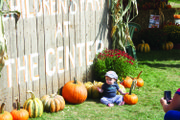 A baby basks in the sun surrounded by pumpkins at The Children's Farm in Palos Park.