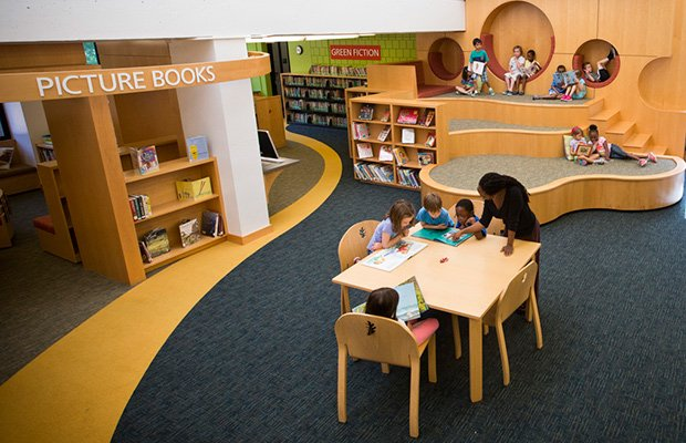 Kindergarten teacher Nicole Siverls helps her class read picture books in the Park School library.