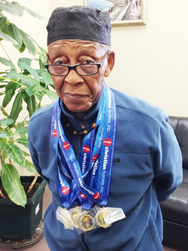 Baba Griot Leonard Lucas poses with his most recent Illinois Senior Olympic gold medals.