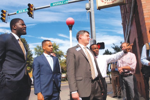 Kasib Sabir points out a problem spot on Intervale Street to mayoral candidate John Connolly during a tour of Grove Hall. Looking on are Tony Richards and Michael Williams. (Yawu Miller photo)