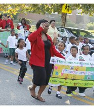 The Empowerment Academy celebrated 10 years of excellence with a parade on Friday, October 4, 2013. (Above) Pre-Kindergarten teacher E. Gray with students from her class, Kennedi S. Joshua T., Ne'vaeh R., DeShawn R. and Pre-Kindergarten Assistant P. White; and Destiny C. (black slacks and white shirt) high steps along the parade route.