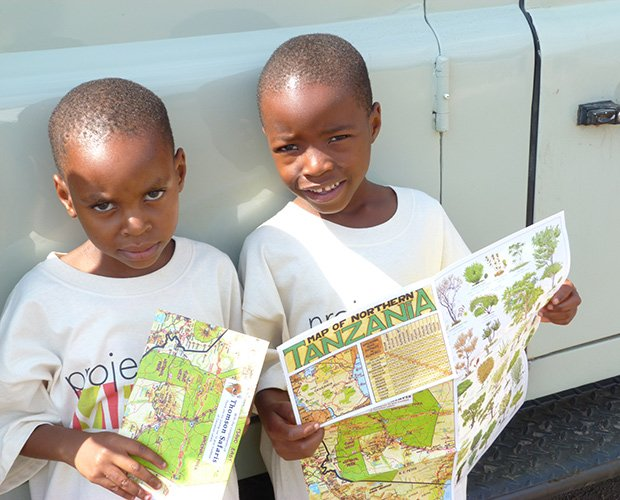 Primary school students sponsored by Project MEMA on Safari. Asha, Gifty, Beatrice and Emanueli are the first people in their families to see safari animals in person because of the high cost to attend a safari tour in Tanzania.  (Photo courtesy of Project MEMA)