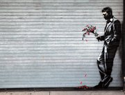 """English Graffiti artist Banksy's latest work is displayed on a metal roll-up door at the Hustler Club on 51st and West street in New York City's Hell's Kitchen with the caption """"Waiting in vain … at the door of a club."""""""