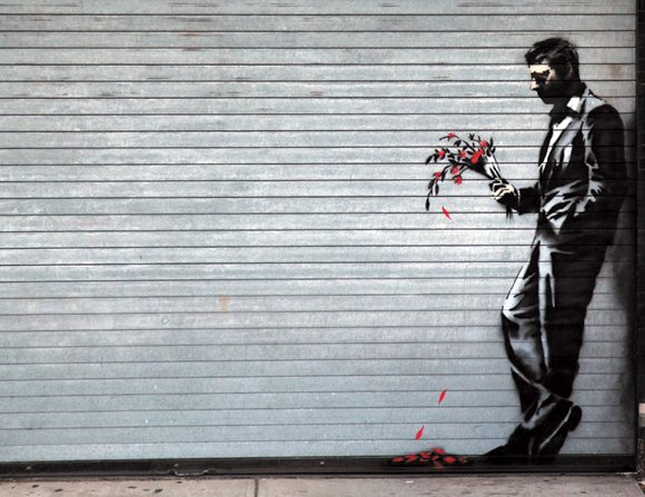 "English Graffiti artist Banksy's latest work is displayed on a metal roll-up door at the Hustler Club on 51st and West street in New York City's Hell's Kitchen with the caption ""Waiting in vain … at the door of a club."""