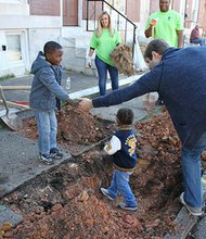 """Volunteers from BGE and Hogan Lovells law firm received """"help"""" from some youngsters as they planted trees throughout McElderry Park in southeast Baltimore on Friday, October 18, 2013."""