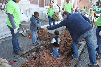 "Volunteers from BGE and Hogan Lovells law firm received ""help"" from some youngsters as they planted trees throughout McElderry Park in southeast Baltimore on Friday, October 18, 2013."