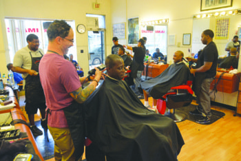 Michael Brown (forefront), owner and head barber of A Sharper Image, shares a laugh with a customer as he cuts his hair. When Brown opened the barbershop on Georgia Avenue in 2001, barbers Raun 'Ron' Giles and Errol Wilson (pictured in the background) joined him to become part of what is now a six-man team of highly skilled professional barbers.