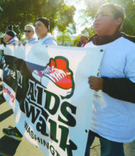 Thomas Howard (right), 12, helps to carry the AIDS Walk banner during the 27th Annual AIDS Walk on Saturday, Oct. 26.